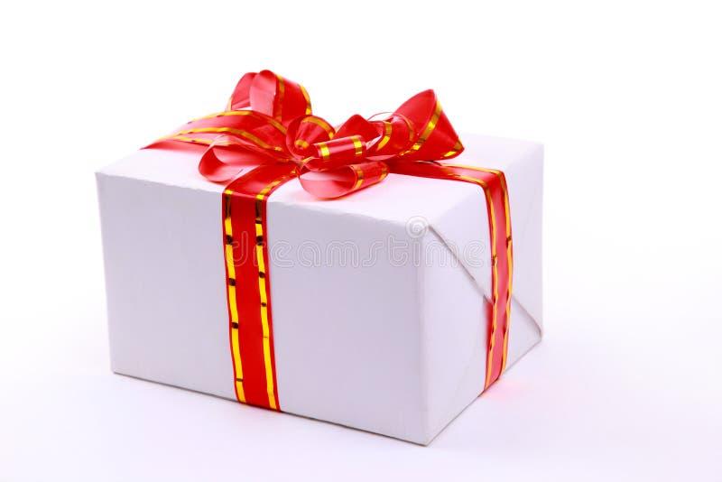 Ein weißer Geschenkkasten mit rotem Farbband lizenzfreie stockbilder