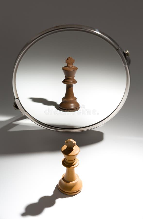 Ein weißer König schaut in einem Spiegel, um sich als schwarzer König zu sehen lizenzfreie stockfotografie