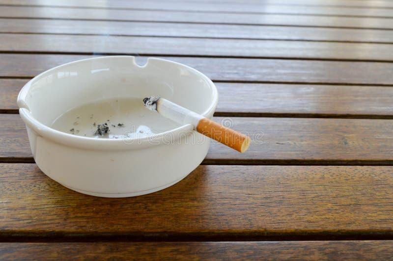 Ein weißer keramischer Aschenbecher mit einer Zigarette und einer Asche mit einem schwarzen Feuerzeug für rauchende Stände auf ei lizenzfreies stockfoto