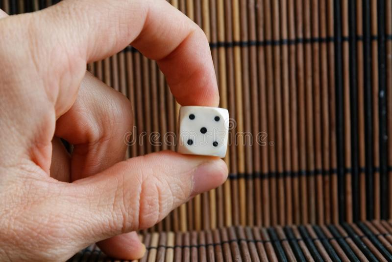 Ein weißer Plastik würfelt in Mann ` s Hand auf braunem Holztischhintergrund Sechs Seitenwürfel mit schwarzen Flecken Nr. 5 lizenzfreie stockfotografie