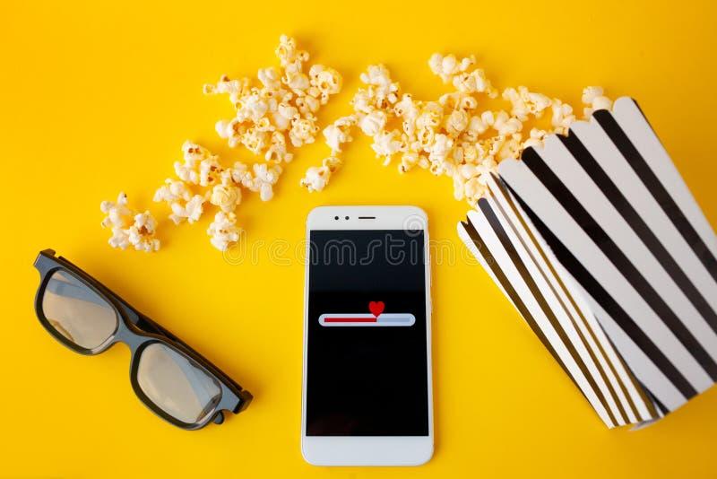 Ein weißer Smartphone mit smilies auf dem Schirm, den Gläsern 3d, einem Schwarzweiss-Papier- mit Leselinienkasten und zerstreutem stockfoto