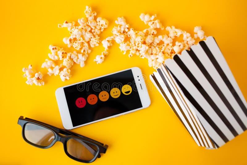 Ein weißer Smartphone mit smilies auf dem Schirm, den Gläsern 3d, einem Schwarzweiss-Papier- mit Leselinienkasten und zerstreutem lizenzfreie stockbilder
