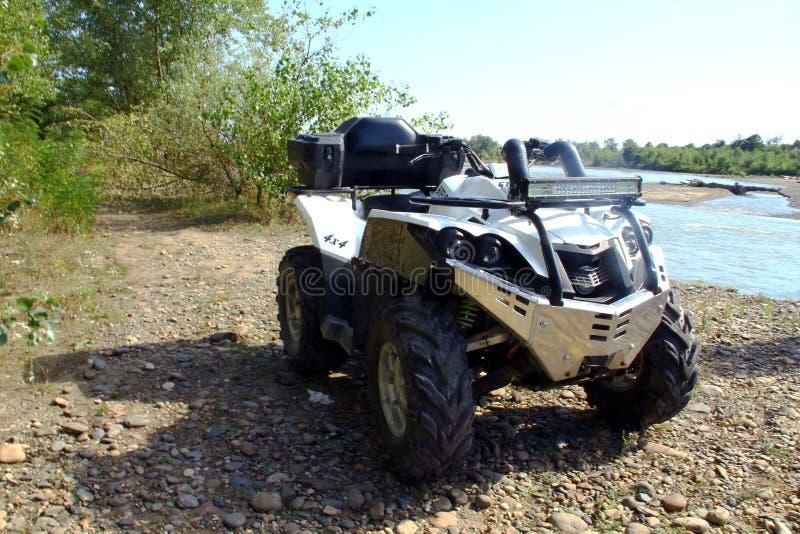 Ein weißes ATV steht an einem sonnigen Tag durch den Fluss lizenzfreies stockbild