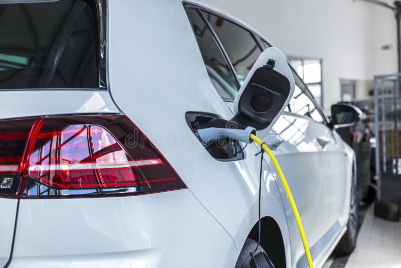 Ein weißes Auto, das mit Strom aufgeladen wird Eine neue Generation von Autos stockfotos