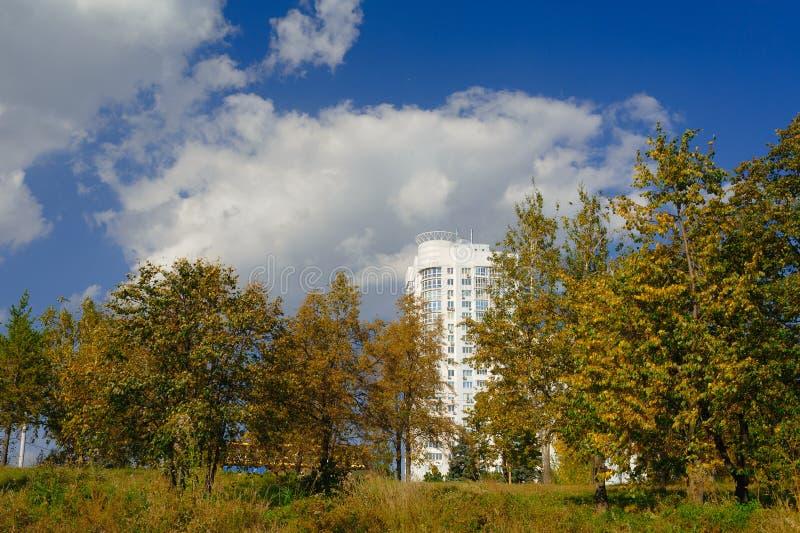 Ein weißes Gebäude mit 25 Geschichten glänzt durch das Herbstlaub stockfotografie