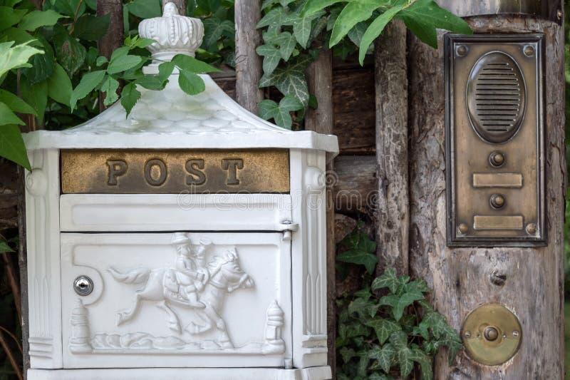 Ein WeißmetallBriefkasten mit dekorativen Elementen hängt am Zaun nahe bei der Glocke und der Wechselsprechanlage lizenzfreie stockfotografie