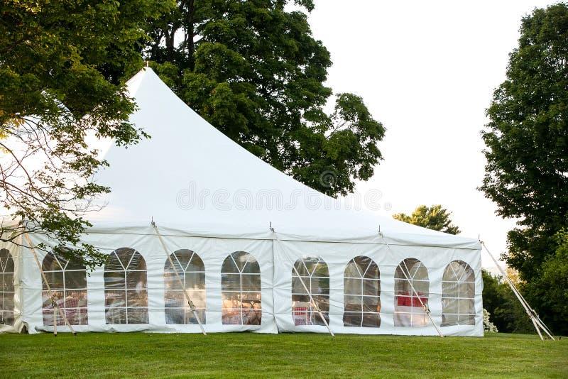 Ein weißes Heiratszelt gegründet in einem Rasen umgeben durch Bäume und mit den Seiten unten stockbilder