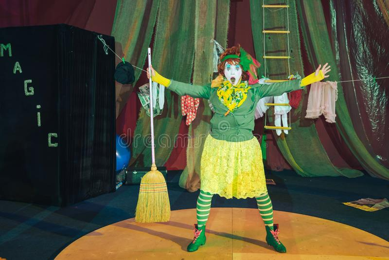 Ein weiblicher Clown in einem Stadiumsbild mit einem Besen lizenzfreie stockfotografie