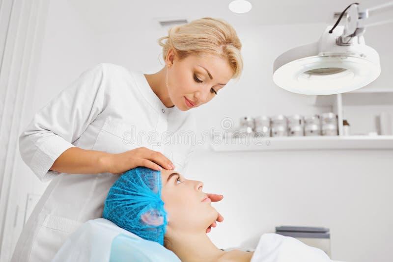 Ein weiblicher Cosmetologist überprüft das Gesicht eines Mädchens lizenzfreies stockfoto