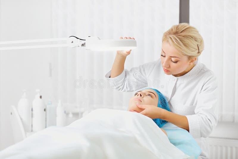Ein weiblicher Dermatologe überprüft das Gesicht eines Mädchens lizenzfreies stockfoto