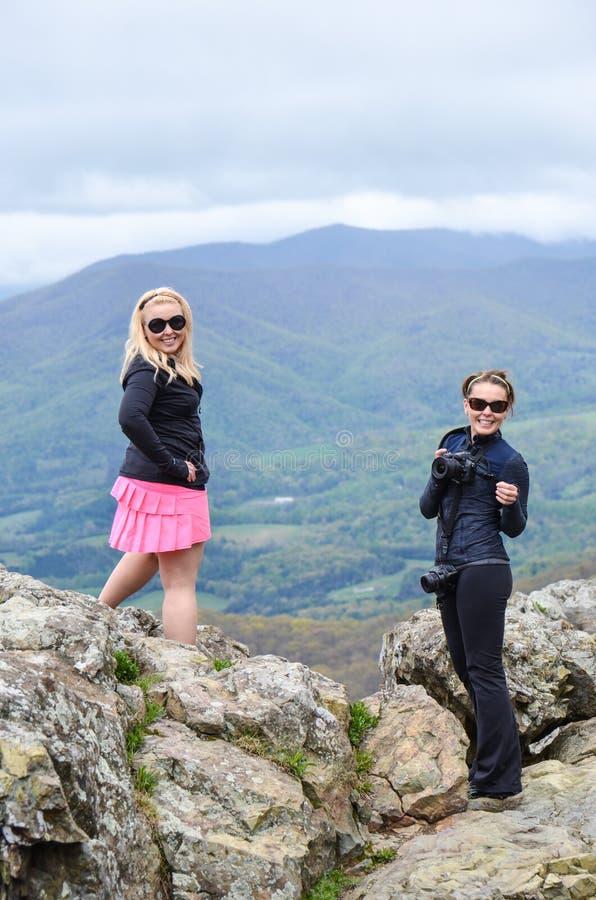 Ein weiblicher Fotograf und ihr Modell werfen für Fotos an der Spitze des steinigen Mannes Mountai auf lizenzfreie stockbilder