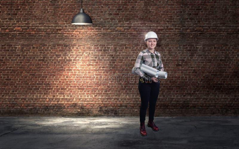 Ein weiblicher Ingenieur im weißen Sturzhelm gegen Wandhintergrund des roten Backsteins 3d übertragen Elemente in der Collage stockbild