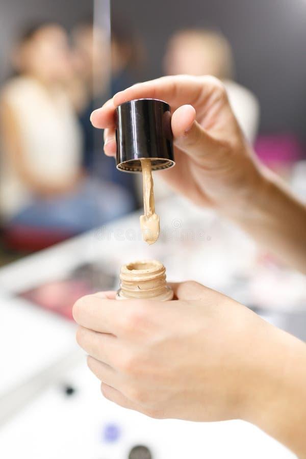 Ein weiblicher Make-upkünstler, Griffe eine Grundlage in ihrer Hand stockfotografie