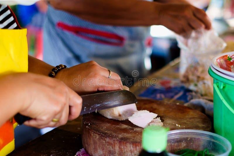 Ein weiblicher Straßenhändler, der Schweinefleisch für das Kochen schneidet stockfotografie