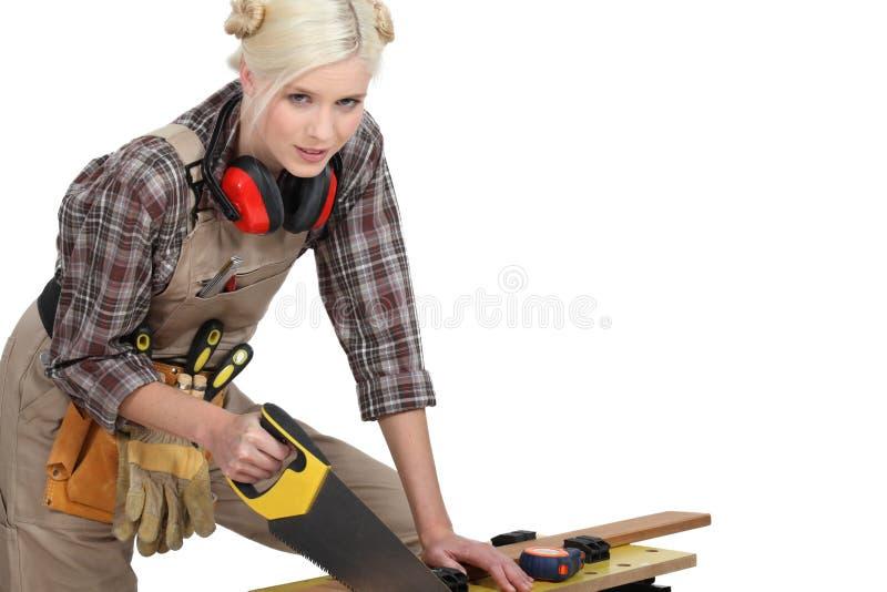 Ein weiblicher Tischler Sawing. lizenzfreie stockfotografie