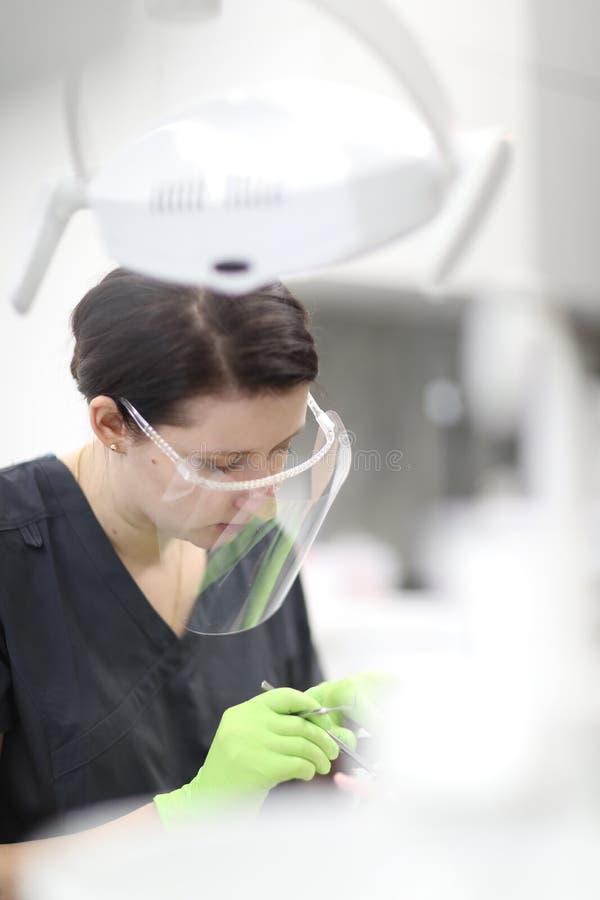 Ein weiblicher Zahnarzt überprüft die Mundhöhle eines Patienten stockfoto