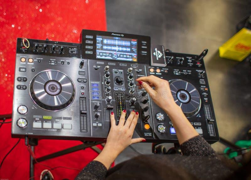 Ein weibliches DJ, das mit einer Pionierkonsole in Cagliari, Sardinien im November 2018 spielt lizenzfreie stockfotos