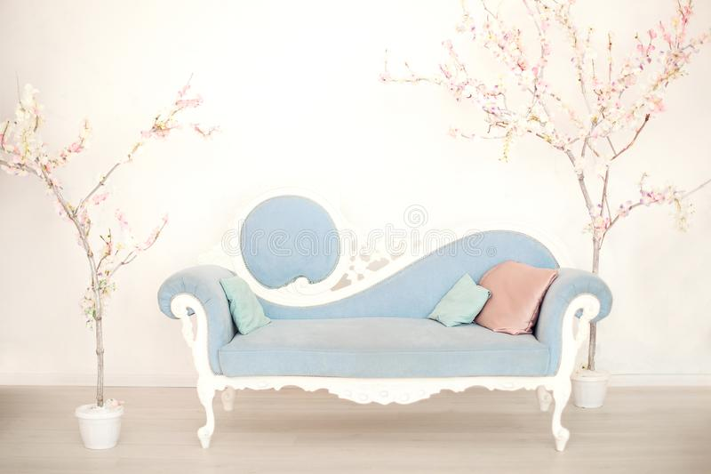 Ein weiches blaues Sofa mit künstlichen blühenden Bäumen in einem weißen Wohnzimmer Klassisches Artsofa im Haus Antikes hölzernes stockfotos