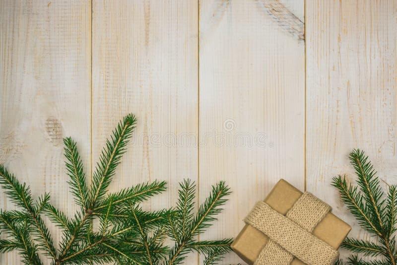 Ein Weihnachtsaufbau Weihnachtsgeschenk, Kiefernkegel, Tannenzweige auf hölzernem weißem Hintergrund Flache Lage, Draufsicht, Kop lizenzfreies stockfoto
