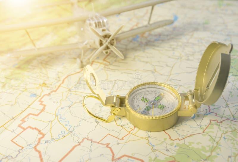 Ein Weinlesekompaß auf der Karte und einem Flugzeug stockbild