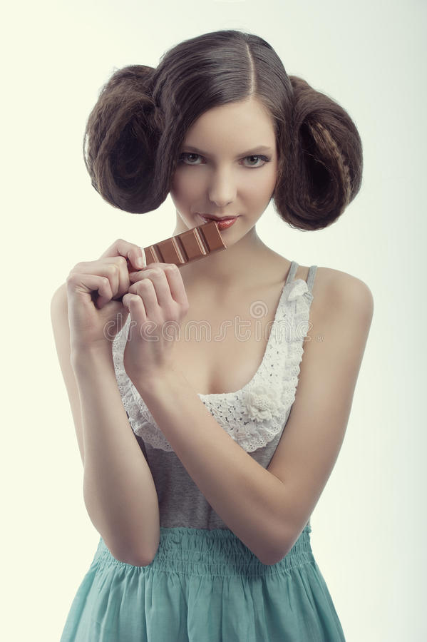 Ein Weinlesemädchen, das Schokolade isst lizenzfreies stockbild