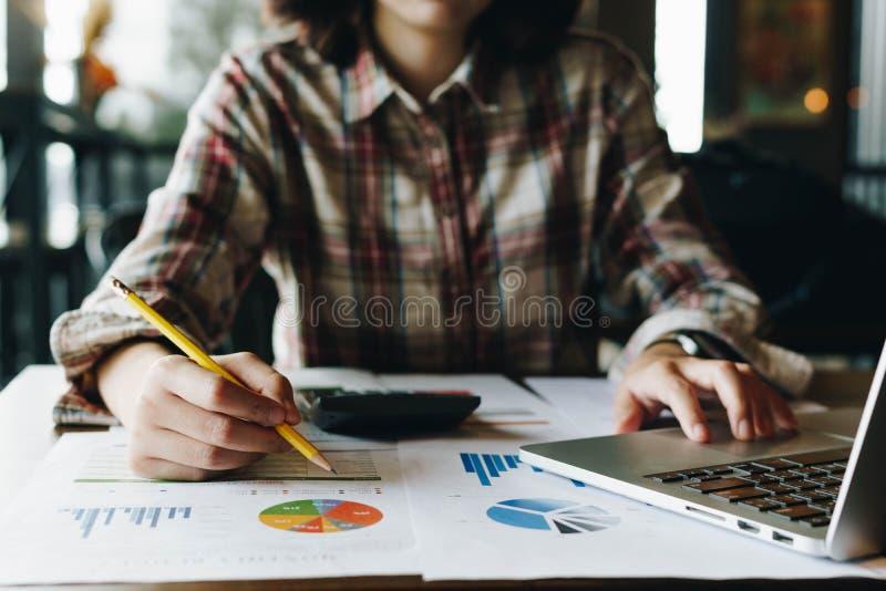 Ein Wirtschaftsprüfer unter Verwendung eines Taschenrechners für die Berechnung mit Finanzrepräsentanten lizenzfreies stockfoto