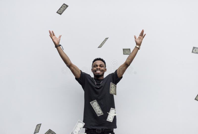 Ein wohlhabender afrikanischer Mann, der sein Geld wegwirft lizenzfreie stockbilder