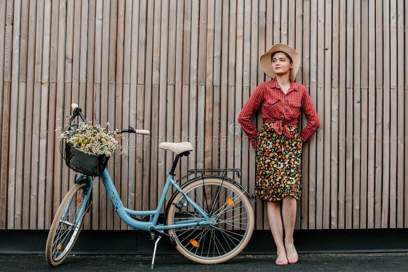 Ein wunderbares Mädchen reist mit dem Fahrrad Gehen in das Freien Schönheit mit einem Korb von Blumen Fahrradfahrt stockfotografie