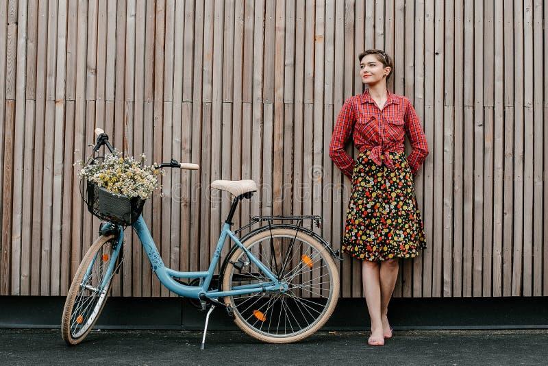 Ein wunderbares M?dchen reist mit dem Fahrrad Gehen in das Freien Sch?nheit mit einem Korb von Blumen Fahrradfahrt stockbild
