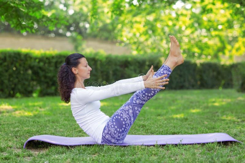 Ein Yogamädchen, das in einem sonnigen Park ausarbeitet Einfache Morgenübungen Entspannende asanas Praxis Gesundes Mädchen auf ei stockfotos