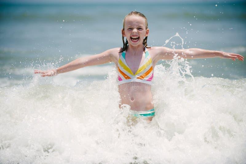 Ein Yong-Mädchen in den brechenden Wellen. stockfoto