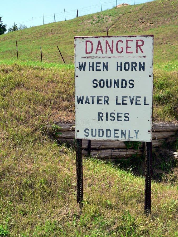 Ein Zeichen zeigt Gefahr auf einem Hügel an - wenn Hupen-Ton-Wasserspiegel plötzlich steigt stockbilder