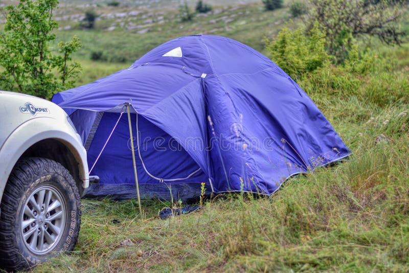 Ein Zelt in den Bergen und in der Maschine im Ruhezustand stockfoto