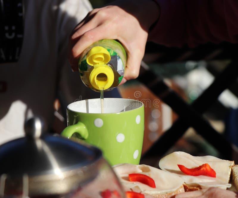 Ein zitronengelber Saft, der zur grünen, beschmutzten Schale für Snack gewöhnt Auch es gibt Brot mit Schinken und rotem Pfeffer S stockfoto