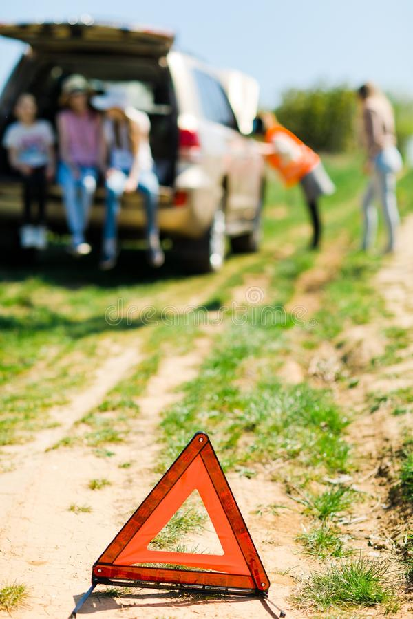 Ein Zusammenbruchdreieck steht nahe einer defekten Motor- Familie mit Kindern lizenzfreie stockfotos