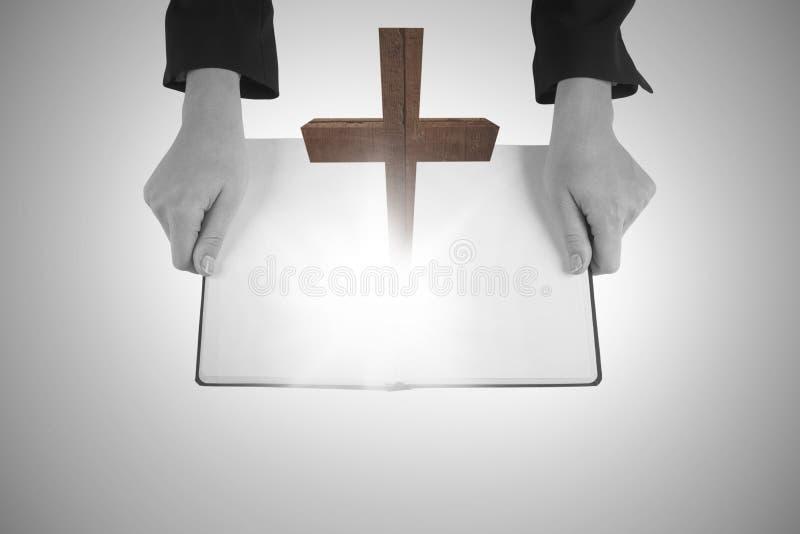 Ein zusammengesetztes Bild von den Händen, die ein offenes Buch halten stockbild