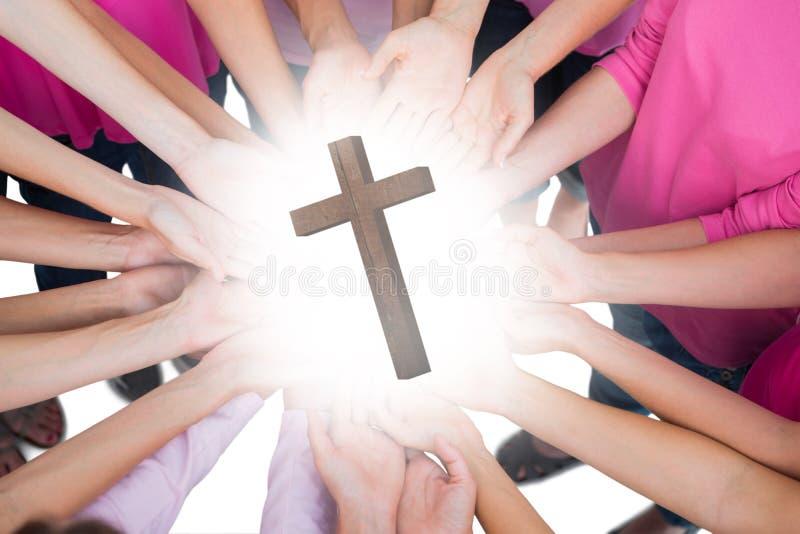 Ein zusammengesetztes Bild von den Händen verbunden im Kreis, der Brustkrebs-Kampfsymbol hält stockbilder