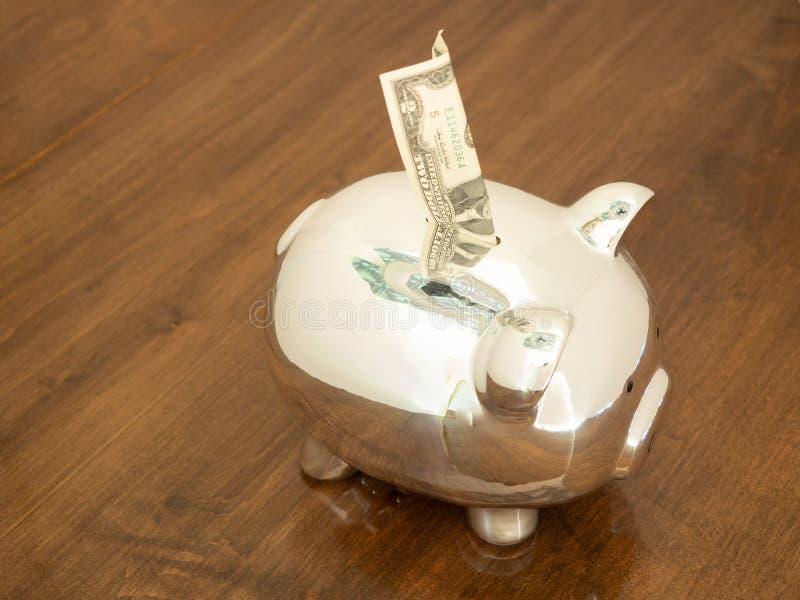 Ein zwei Dollar Bill Going in ein glänzendes Sparschwein lizenzfreie stockfotos