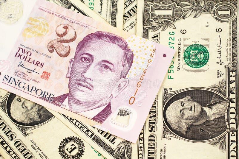 Ein zwei Dollarschein von Singapur mit Amerikaner ein Dollarscheine stockfotos