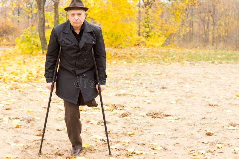 Einbeiniger Mann, der mit Krücken im Park geht stockfotos