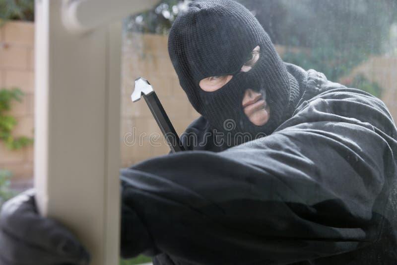 Einbrecher Breaking Into House lizenzfreies stockbild
