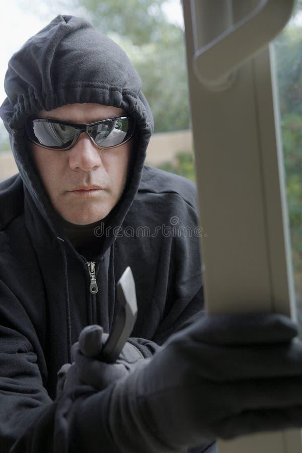 Einbrecher Breaking Into House stockfoto