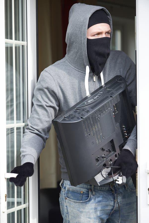 Einbrecher Breaking Into House und Diebstahl-Fernsehen lizenzfreie stockfotos