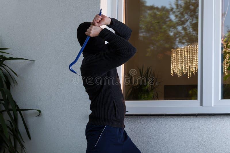 Einbrecher bricht das Fenster stockfotografie