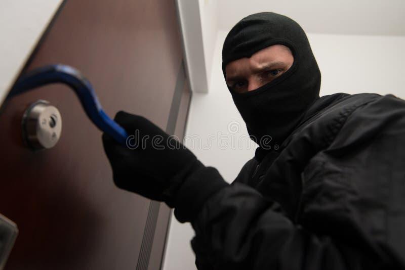 Einbrecher bricht in ein Wohngebäude ein stockbild