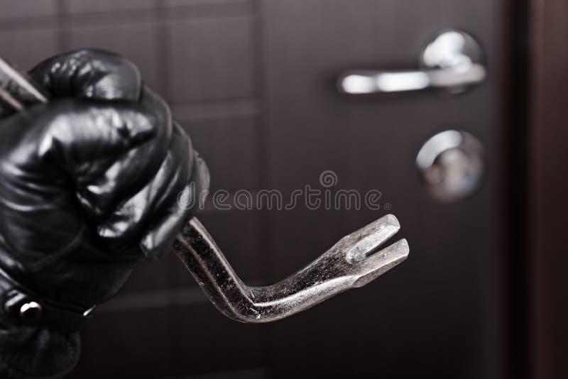 Einbrecherhandholdingbrechstangebruch-Öffnungstür stockfotos