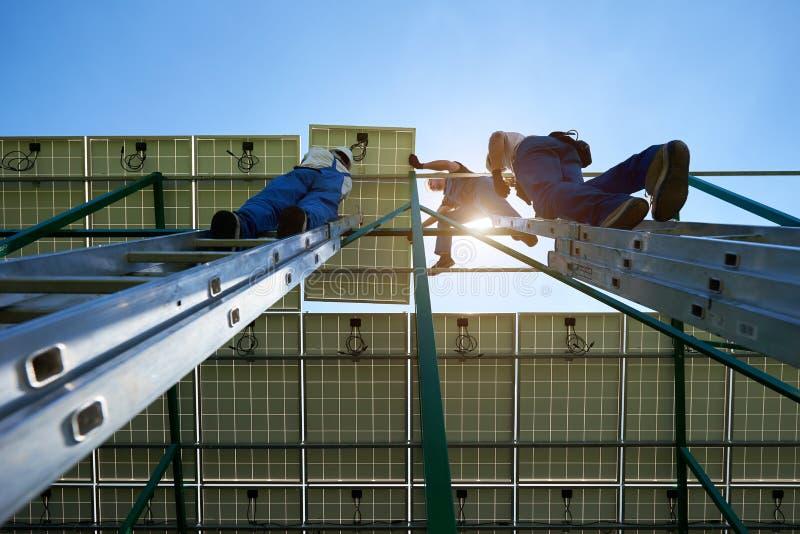 Einde van zonnepanelen die het werk door het team van beroepsarbeiders opzetten stock afbeeldingen
