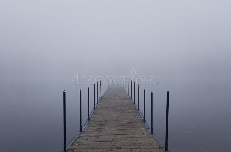 Eindeloze pier in een mist stock fotografie
