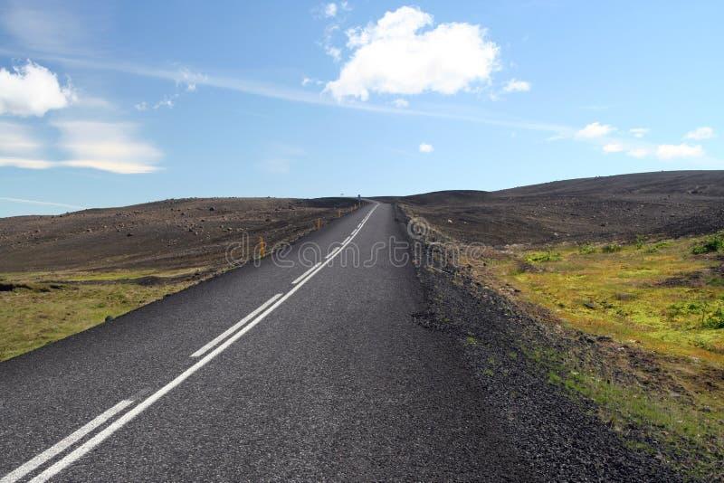 Eindeloze rechte asfaltweg in onvruchtbaar breed landschap stock afbeelding