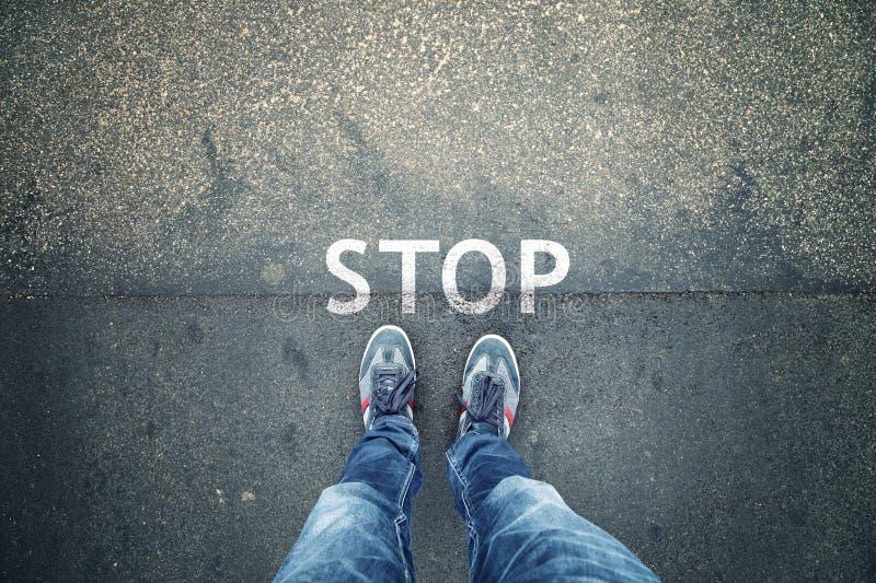 Eindeteken op straatvloer met de mens stock afbeelding